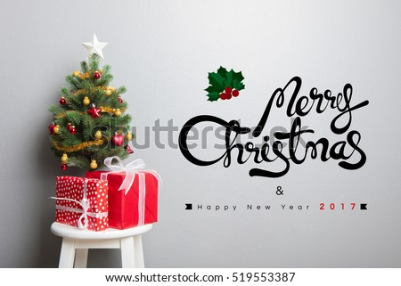 Gift boxes and small decorated Christmas tree on stool chair with MERRY CHRISTMAS and HAPPY NEW YEAR 2017 text on the wall