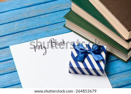 Gift boxes, books and paper with My Book words on blue background