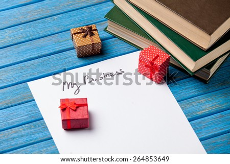 Gift boxes, books, pencil and paper with My Business words on blue background