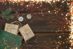Gift boxes in kraft paper decorated with golden snowflakes come out of a green paper bag and lie on wooden background. Multi-colored bokeh lights. New Year's shopping. Christmas New Year concept