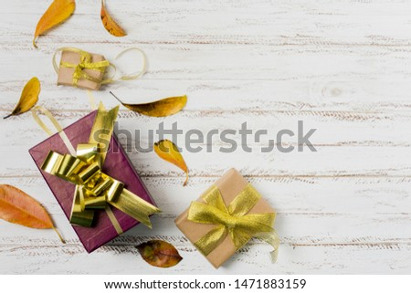 Gift boxes in wrapping paper with ribbons and autumn leaves on a white wooden background #1471883159