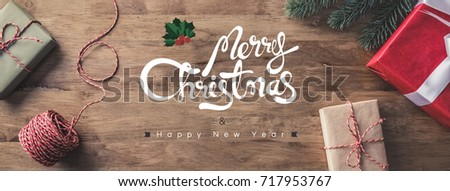 Gift boxes on a wooden table with Merry Christmas and Happy New Year greeting texts - horizontal web banner #717953767