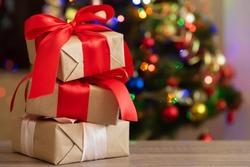 Gift boxes with large red ribbon against Christmas tree and defocused bokeh. Soft focus. Copy space. Christmastime celebration concept