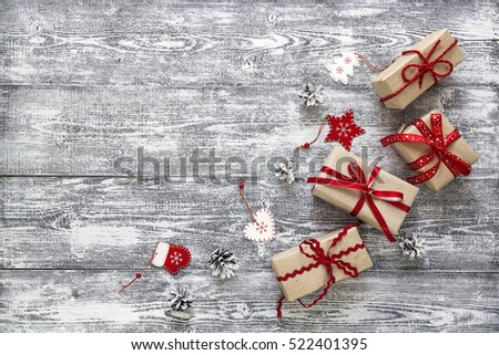 Gift boxes with red ribbon, Christmas decorations and pine cones on gray wooden table. Christmas background. Space for text. Top view.