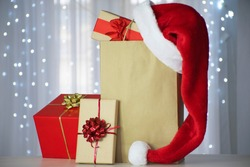 Gift boxes with Santa hat over paper bag with Christmas lights bokeh  on background. New Year and Christmas celebration, Boxing Day, delivery or festive shopping for holidays. Copy space mockup.