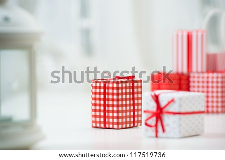 Gift boxes with xmas presents wrapped in red paper with ornament. Lots of copyspace