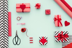Gift boxes wrapped in red checked paper and the contents of a workspace composed. Flat lay. Valentines day, Christmas (xmas) or New year gift packing. Holiday decor concept.