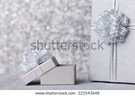 gift boxs with silver ribbon, glittery silver background