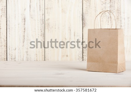 Gift cardboard shopping bag on wooden table
