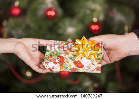 Gift delivery  between a man and a woman in front of Cristmas tree