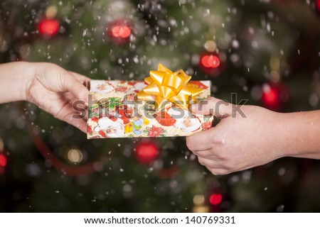 Gift delivery  between a man and a woman under snowfall in front of Cristmas tree