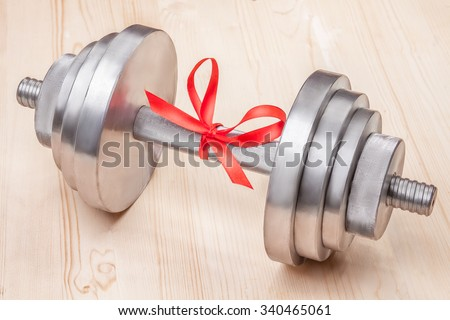 gift - dumbbell tied with red ribbon on wooden desk