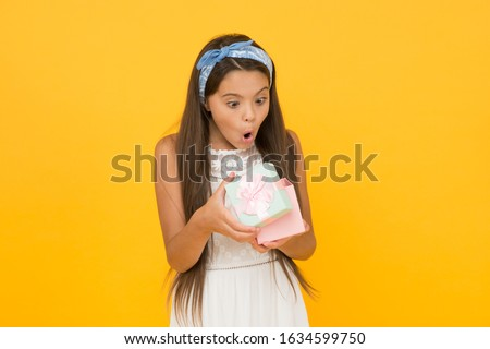 Gift for anyone who loves to be surprised. Surprised child open present box. Little girl look surprised yellow background. Birthday surprise. Holiday celebration. Souvenir shop. Being surprised.