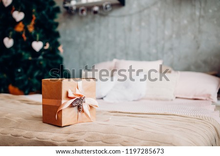 Gift for new year girl in kraft paper, pink ribbon lying on bed loft.