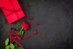 Gift for Valentine's day. Red rose, gift box, red hearts signs on black background top view copy space