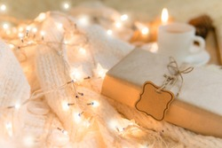 Gift in cozy room. Cold day in warm house. Concept Hygge. Merry Christmas!