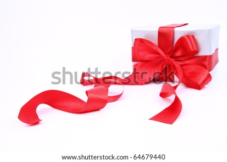 Gift in silver wrapping with a red bow on white background (focus on the ribbon in front)