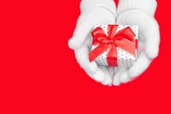 Gift in soft white gloves on a red background with a place for the text. Charity, christmas and holiday discounts concept