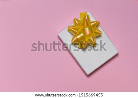 gift on pink background. a white box with a yellow bow. birthday present. christmas present. new year's surprise. top view. space for text.
