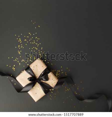 Gift or present box and gold stars confetti on black table top view. Flat lay composition for birthday, mother day, black friday sale, xmas, christmas, new year or wedding.