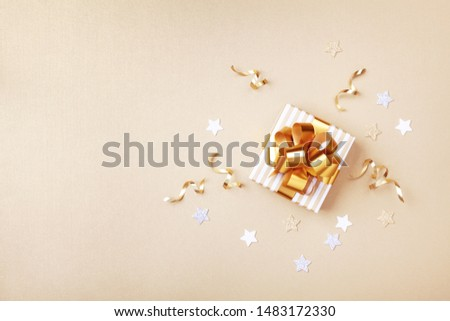 Gift or present box and stars confetti on golden table top view. Flat lay composition for birthday, christmas or wedding.