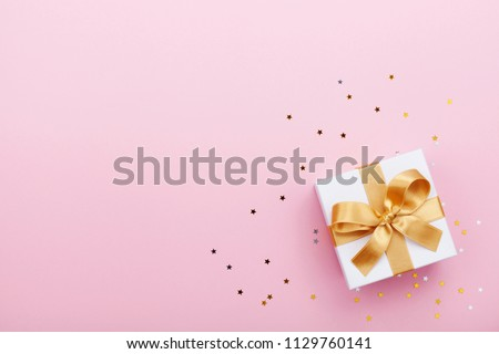 Gift or present box and stars confetti on pink table top view. Flat lay composition for birthday, mother day or wedding.