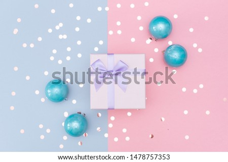 Gift or present box and stars confetti on pink table top view. Flat lay composition for birthday, mother day or wedding