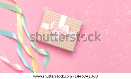 Gift or present box, beautiful festive ribbon, confetti on pink background top view. Flat lay composition for celebration, holiday, birthday Valentine's Day March 8 mother day, wedding. Congratulation