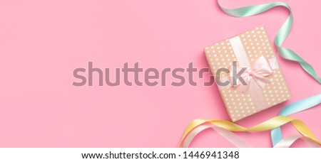 Gift or present box with beautiful festive ribbon on pink background top view. Flat lay composition for celebration, holiday, birthday, Valentine's Day, March 8, mother day, wedding. Congratulation