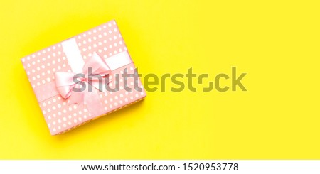 Gift or present box with beautiful festive ribbon on yellow background top view. Flat lay composition for celebration, holiday, birthday, Valentine's Day, March 8, mother day, wedding. Congratulation