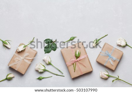 Gift or present box wrapped in kraft paper and rose flower on gray table top view. Flat lay styling. Copy space for text. #503107990