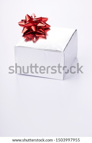 Gift or present, wrapped in silver paper with a red bow on a white background