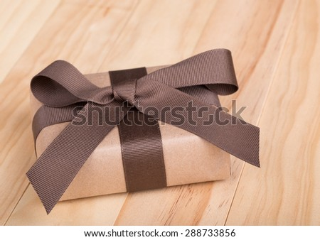 Gift package wrapped in ribbon and bow on wood surface