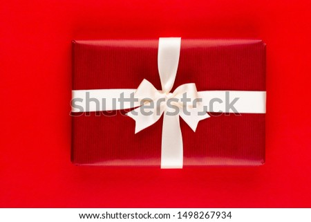 Gift present box on red background top view. Flat lay composition for birthday, mother day or wedding.