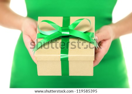 Gift / present. Woman hands showing and giving gifts. Closeup of present made of recycled carton and green ribbon on white background.