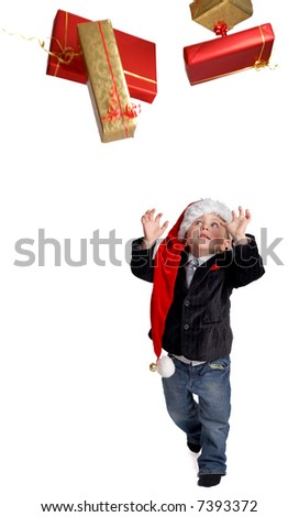 Gift rain. Small boy dressed in smart casual clothes and Santa hat trying to catch gift boxes.