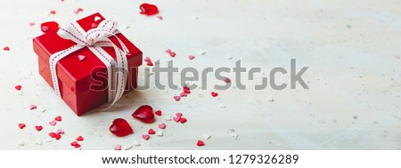 Gift red box with white bow ribbon and hearts on light background for Valentines day. Space for text. Long wide banner