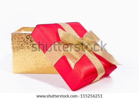 Gift red square box with gild ribbon closeup