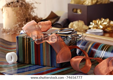 Gift wrapping still life with partially wrapped gift, ribbon and supplies.  Closeup with shallow dof.