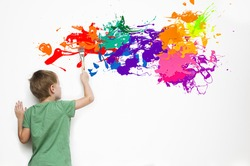 Gifted child drawing an abstract picture with colorful splatters