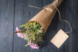 Gifting theme image with a lovely bouquet of flowers wrapped in brown paper and a blank label tied to it, on a black wooden background.