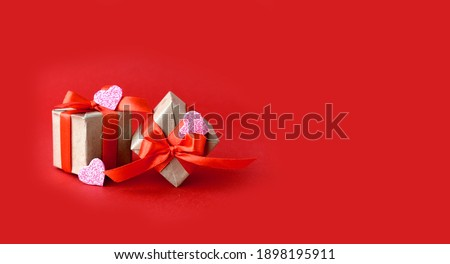 Gifts  and decor hearts  on red background. Minimalist concept for Valentines day Mothers day, Women day or wedding. Greeting banner with copyspace.