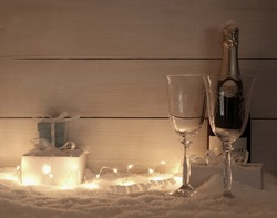 Gifts, Champagne glass and bottle on snow, in evening, fairy lights