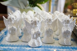 gifts for children in the form of a statuette of an angel. first confession and communion in the church