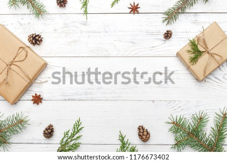 Gifts for new year wrapped in craft paper near spruce branches and cones on white wooden background top view copyspace #1176673402