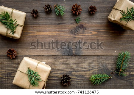Gifts for new year wrapped in craft paper near spruce branches and cones on wooden background top view pattern copyspace #741126475