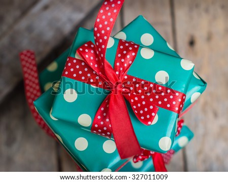 gifts in a beautiful and elegant package on the wooden table. red and turquoise colors. polka dots. top view