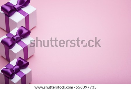 Gifts in a beautiful package, bow from satin ribbon, a few boxes with gifts standing in a row, the attributes of the festive mood, the gift set on a pink background