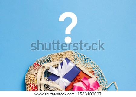 Gifts in a fashionable shopping bag on a blue background with a question mark. Gift shopping concept, discount, sale. Choice, difficulties of choice, what to give Flat lay, top view