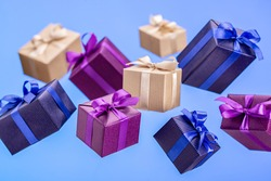 Gifts in flying boxes wrapped in blue, purple and kraft paper with ribbons and bow on  blue background. Holidays and greeting card concept.